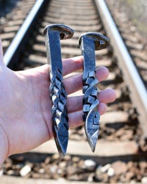 Americký klinec na podvaly s rôznym štýlom rukoväte uchopený v ruke pri železničnej trati