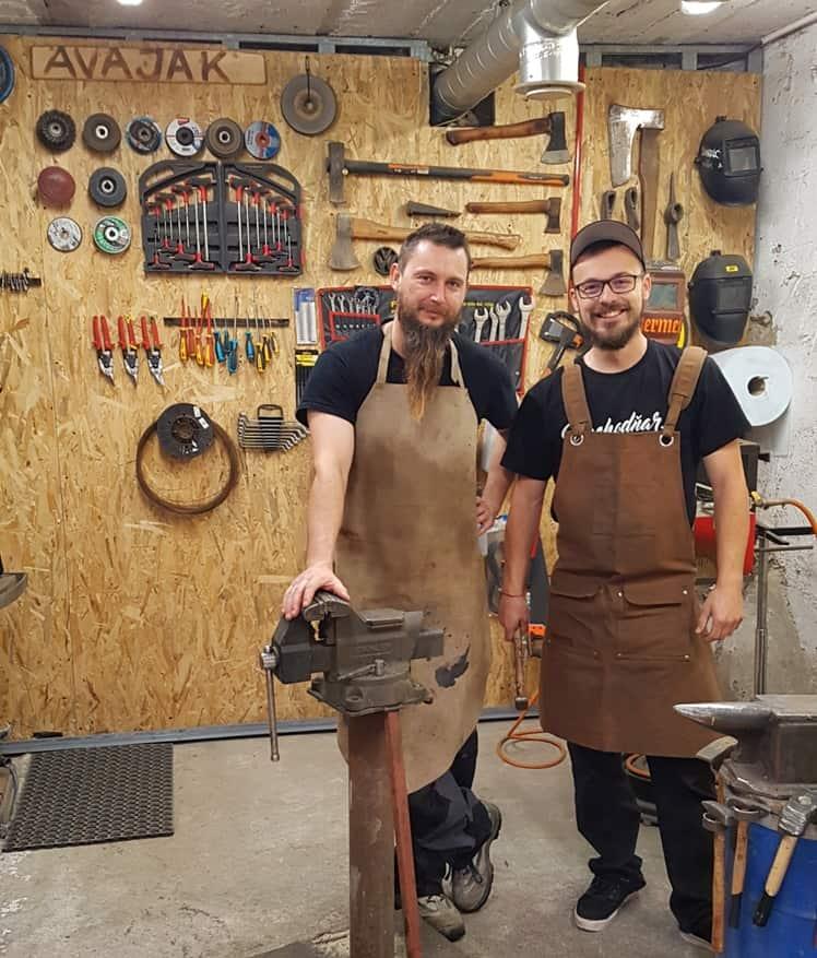 Náš tím priateľských kováčov stojaci v kováčskych zásterách v kováčskej dielni AVAJAK
