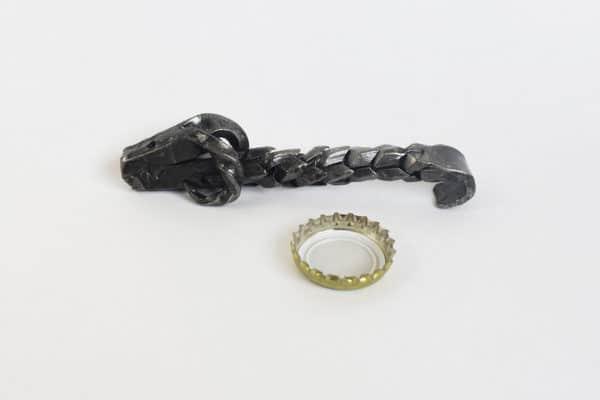 Kovaný otvárak - baran s prispôsobenou rukoväťou vedľa použitého korunkového uzáveru