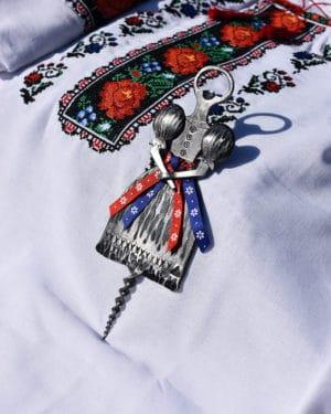 Otvárak Folklóristka ozdobený stuhami vo folklórnom motíve v tvare slovenskej dievky ležiaci na kroji