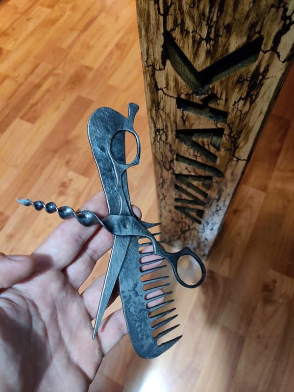 Kovaný hrebeň a kované nožnice tvoria Kadernícky špeciál, ktorý je uchopený v ruke pri vypálenej nožke stola AVAJAK