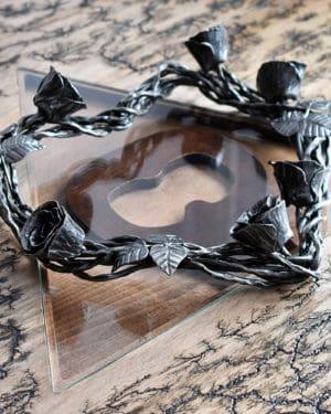 Kovaný veniec v tvare srdca s kovanými ružami a lístkami položený na skle vypáleného stola s AVAJAK logom
