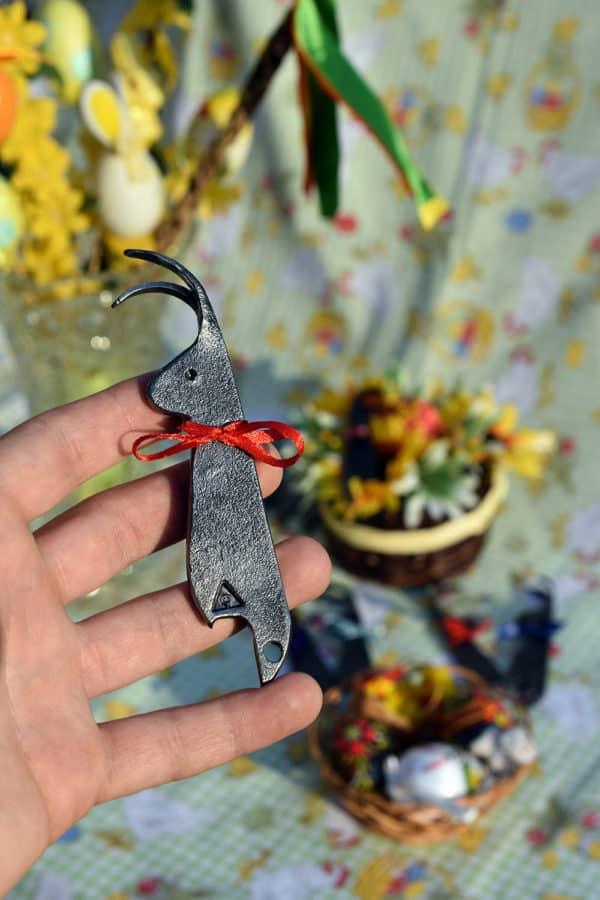 Kovaný zajac ozdobený červenou mašľou uchopený v ruke v motíve Veľkej noci