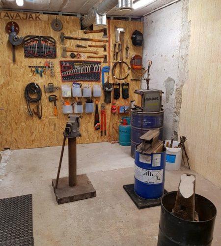 Kováčska dielňa s predmetmi ako vyhňa, nákova, zverák, náradie, sudy, rukavice, sekery, vzduchotechnika