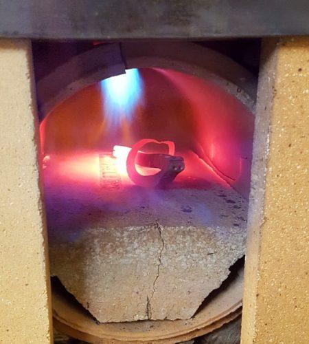 Horiaci plameň v rozpálenej vyhni ohrievajúci oceľový otvárak v tvare kozorožca