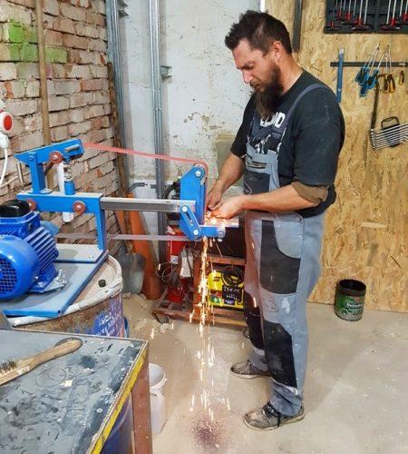 Kováč v pracovnom oblečení brúsi oceľ na pásovej brúske v kováčskej dielni