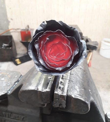 Žeravý oceľový kovaný kvet ruže upevnený vo zveráku