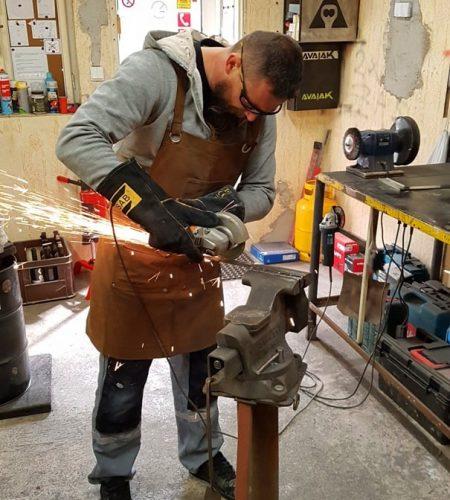 Kováč v kováčskej zástere brúsi oceľový štvorhran upevnený vo zveráku s uhlovou brúskou